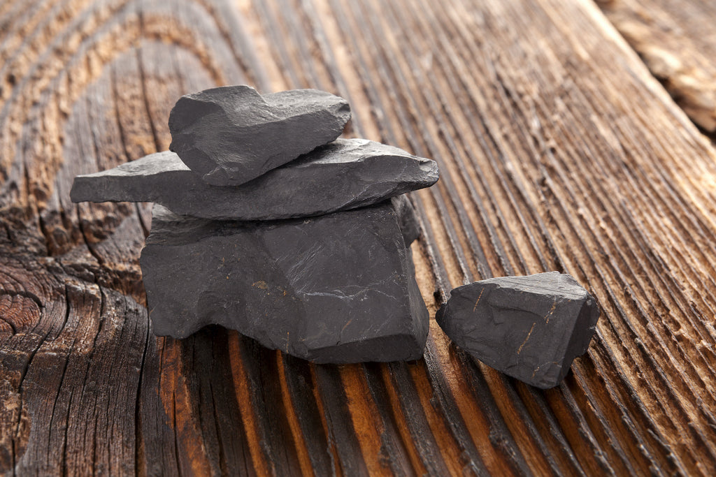 A stack of raw shungite stones on a wood surface