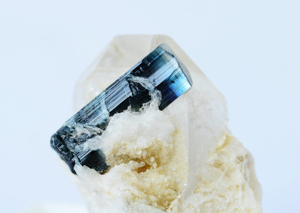A piece of blue tourmaline embedded in surrounding rock