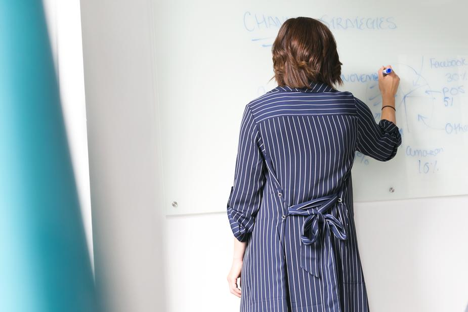 Woman writing on whiteboard in an office.