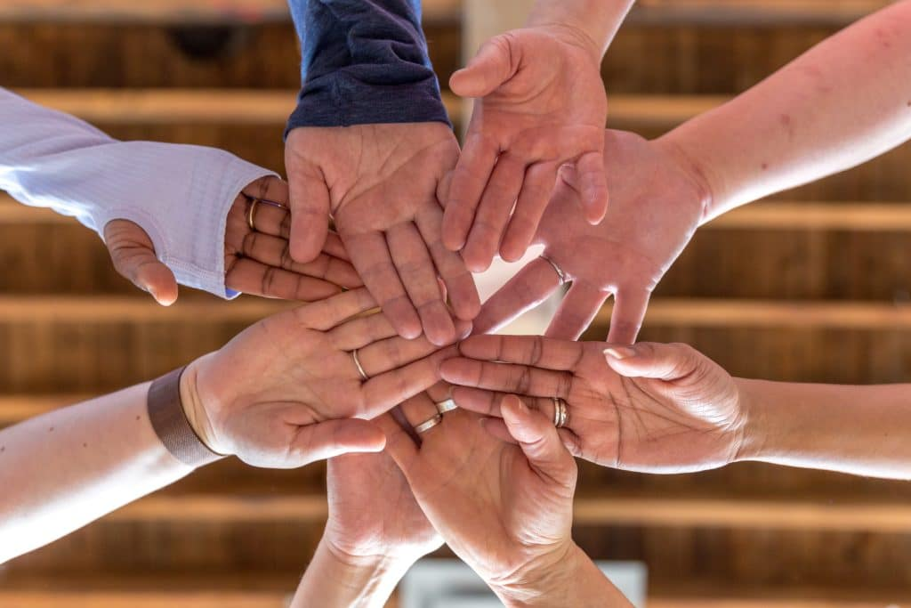 Hands of team in the middle of a huddle