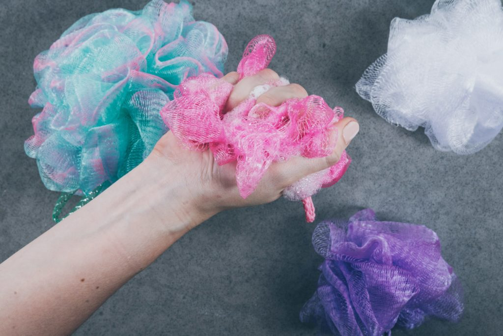 Hand scrunching a soapy pink loofa.