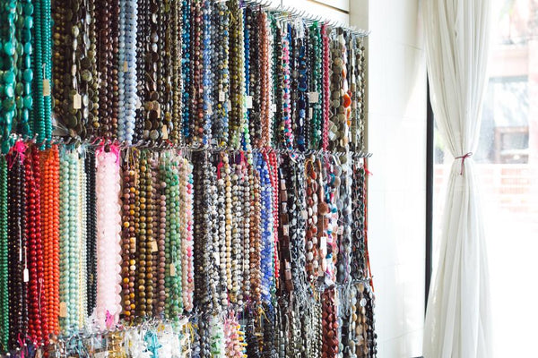 Strings of beads hanging on a shop display.