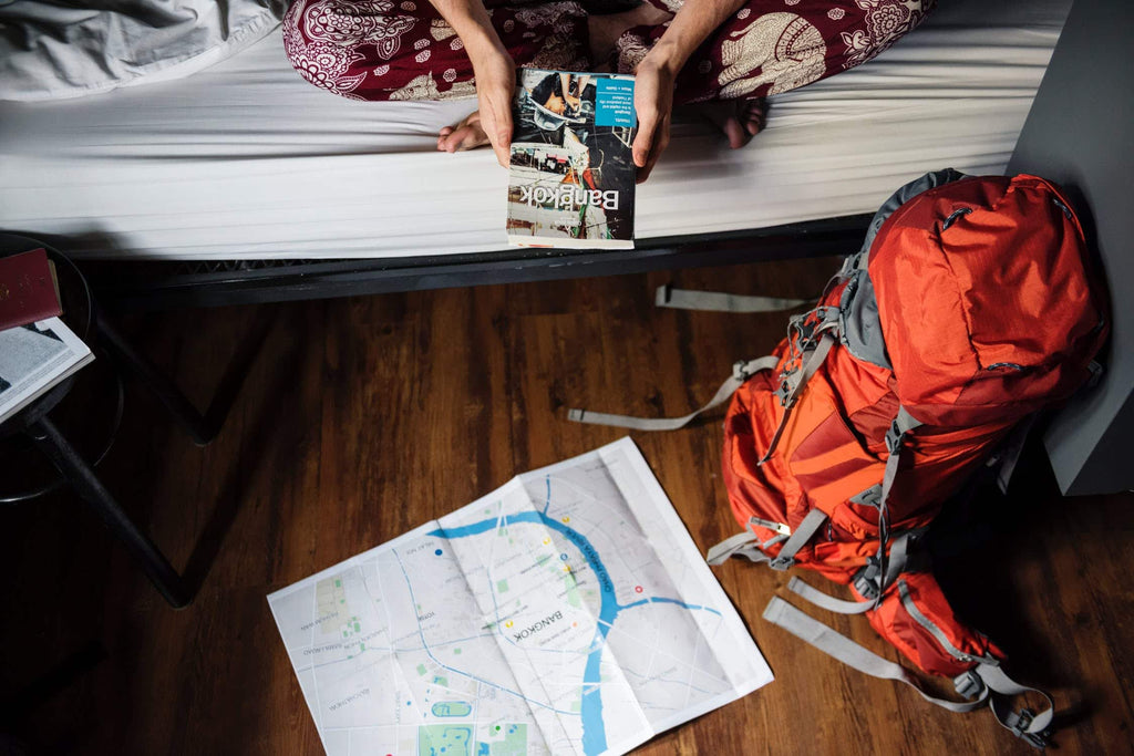 Woman sitting on bed in front of map and backpack.