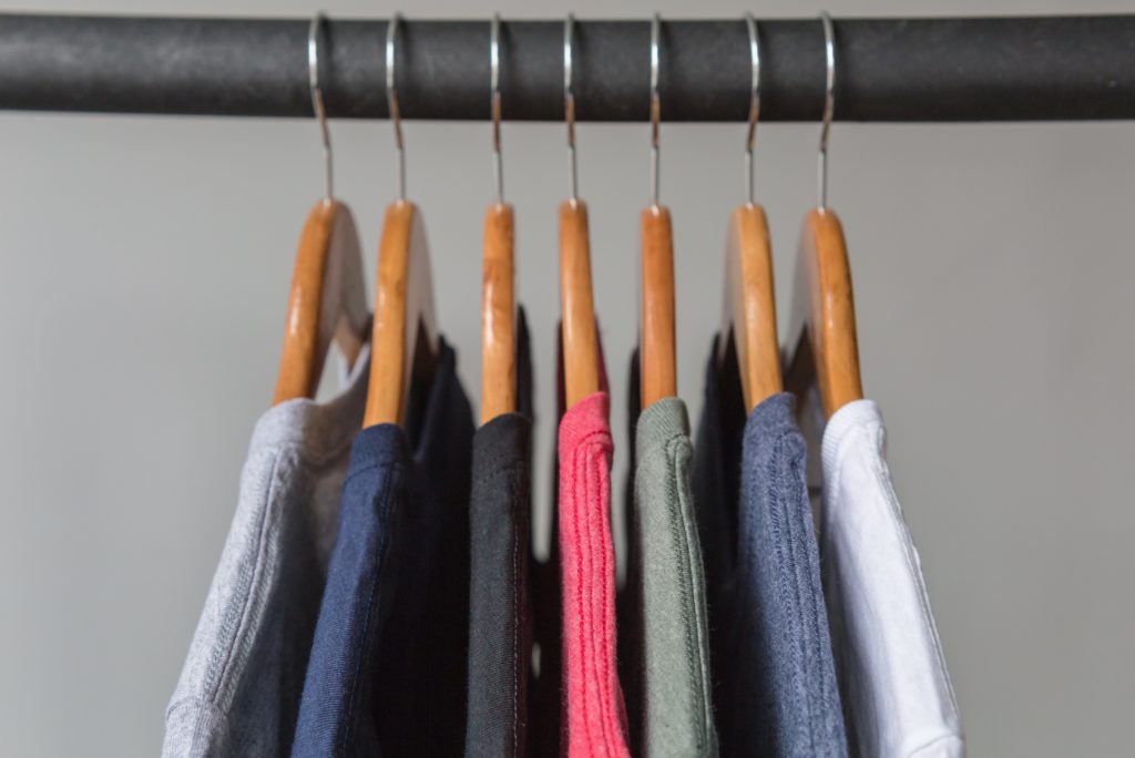 T-shirts on wooden hangers against a grey wall.