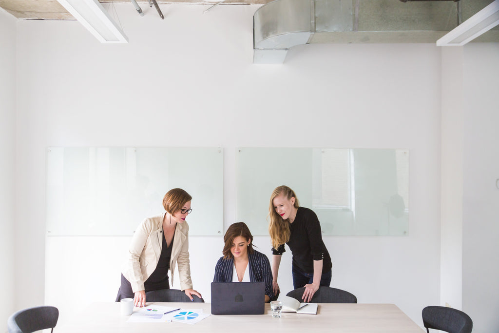 Three women working in an office boardroom.
