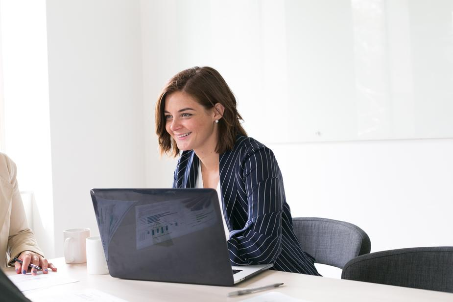 Woman smiling working at desk on laptop.
