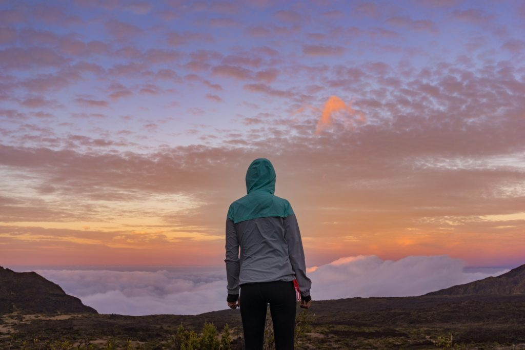 Young woman hiking looking at the sunset.