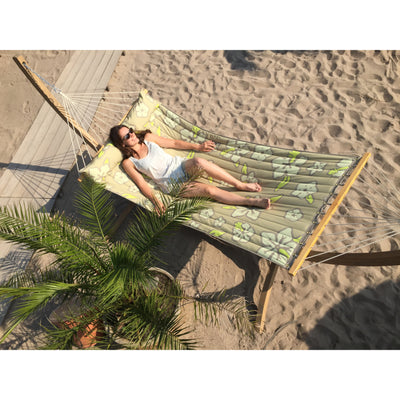 Large wooden hammock stand with hammock and woman relaxing on