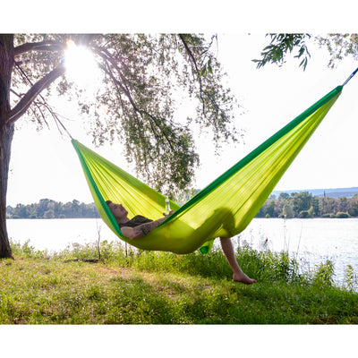 Man relaxing with beer in hammock by lake