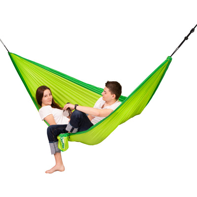 Two people enjoying an outdoor hammock