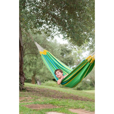 green hammock hung between trees