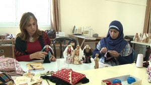Refugee women sewing dolls in memory of the lost villages