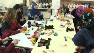 Refugee Women sew dolls at the YWCA to remember the lost villages