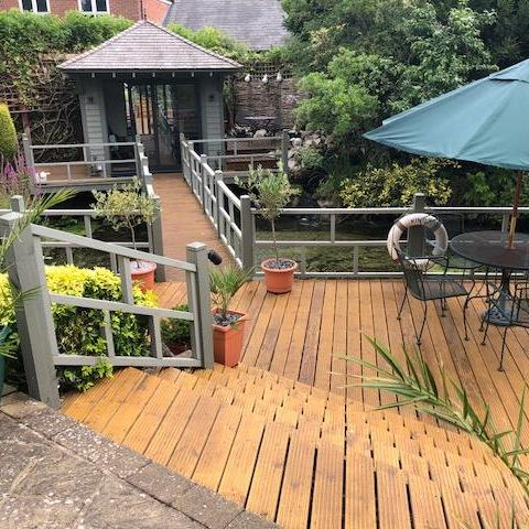 Decking covered with Firmtread Anti Slip Deck Coating. Steps in foreground which lead to a raised platform with garden furniture and shed.