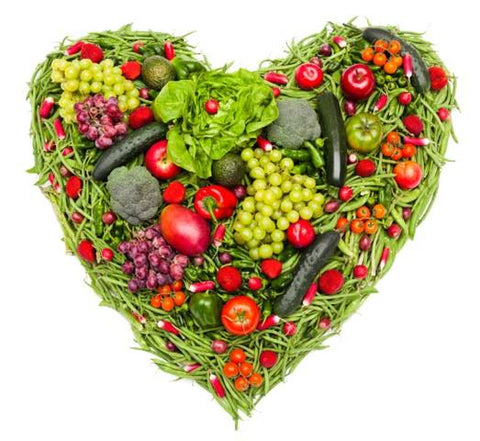 A collection of fresh fruits and veggies placed in a heart shape.