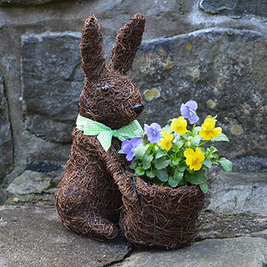 Rabbit topiary planter with yellow and purple flowers in it's basket