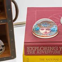 Crystal Domed Paperweight decoupaged with a Art Nouveau Woman's face shown  sitting on a stack of books