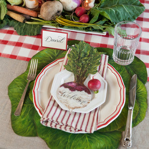 A picture of the green cabbage placemat being used at a table setting. It has white dishes trimmed with red  and a turnip place card.