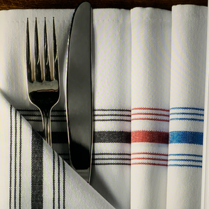 Bistro Striped Napkins in black, red, blue, folded with a fork and knife inserted in the fold.