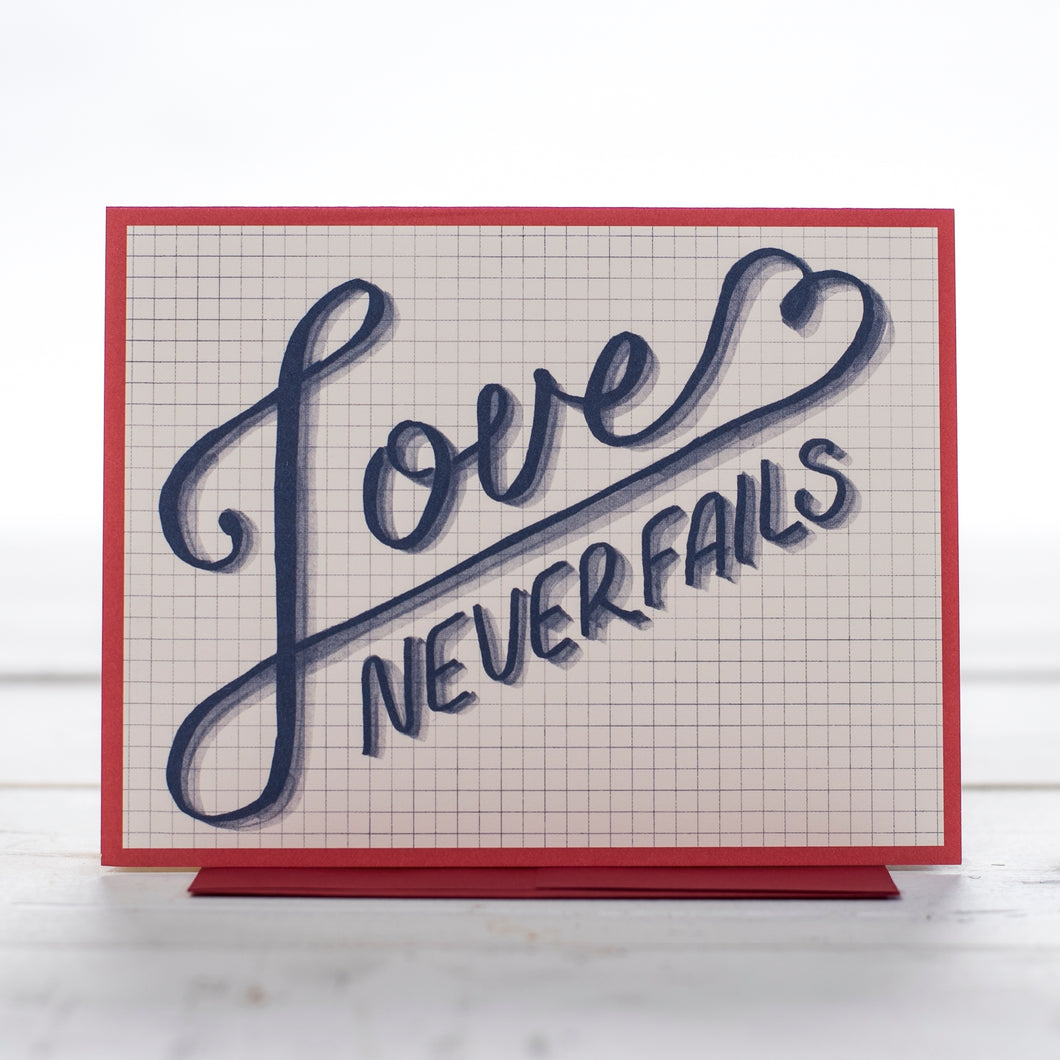 A greeting card with the words Love never fails in blue writing and a red boarder  on a grid back ground