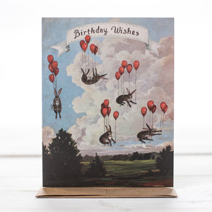 Birthday card message with rabbits floating in the air tied to red balloons. So much fun.