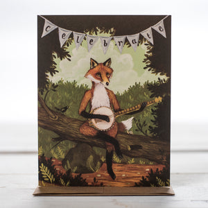 Showing the Fox Celebrate Greeting Gard with a clever Fox sitting on a fallen tree with a banner hanging above his head with the word celebrate spelled out.