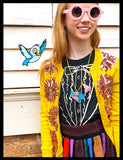 Girl in Sunglasses wearing Bird Necklaces with Blue Cartoon Bird on her shoulder