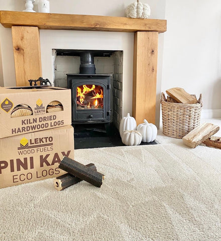 Box of Lekto Pini Kay Eco Logs and kiln dried hardwood logs on a carpet in front of a log burner