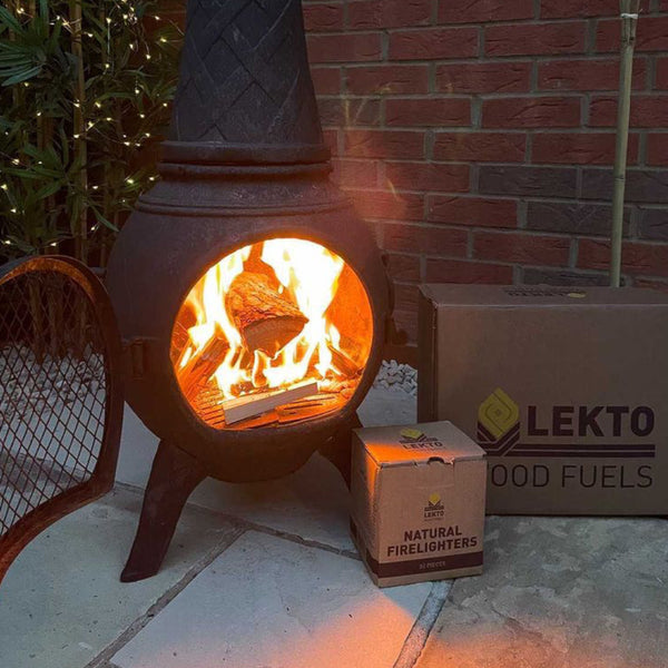 A cast Iron Chiminea with a lit fire next to a box of Natural Firelighters and a box of Wood Fuels