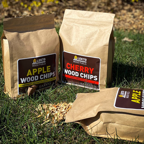 Bags of Lekto Wood Fuels Apple Wood Chips and Cherry Wood Chips on a lawn