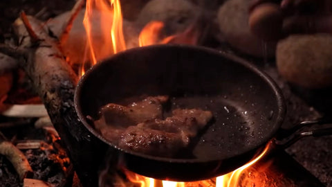 Meat cooked in a skillet on an open fire.