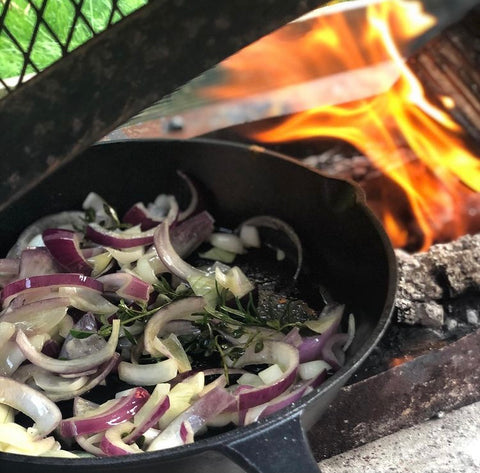 Onions in a frying pan being cooked outdoors
