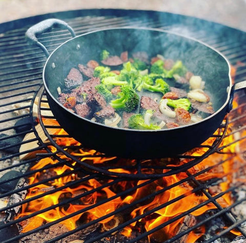 Meat and Vegetables being cooked outdoors in a frying pan over a firepit