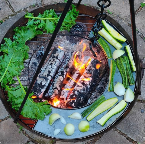 Vegetables being cooked over an outdoor firepit