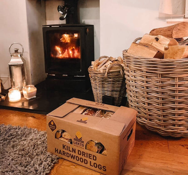 A Box Of Kiln Dried Hardwood Logs In Front Of A Wood Burning Stove