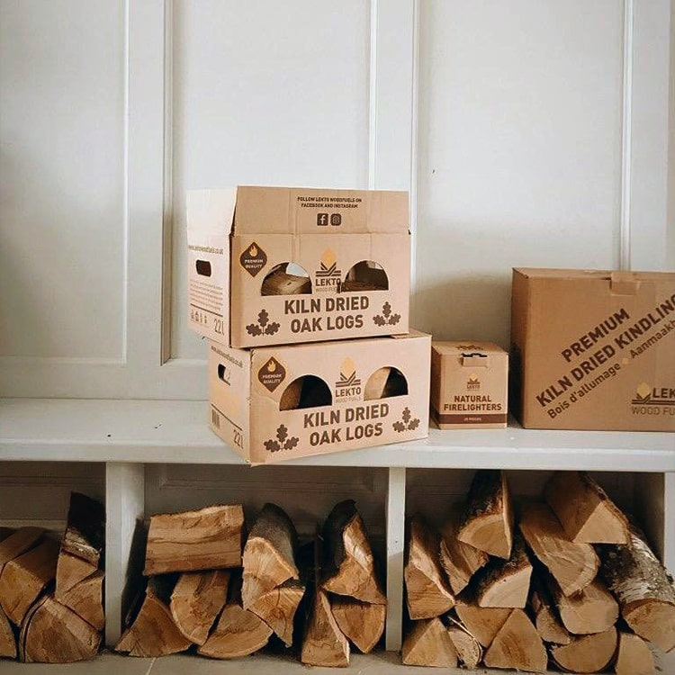 2 stacked boxes of Kiln Dried Oak Logs next to a box of natural firelighters and kiln dried kindling on a bench with firewood stored underneath