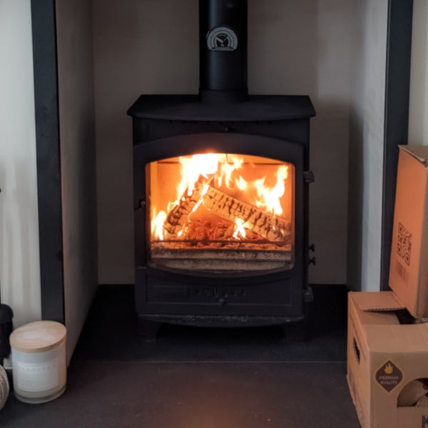 A Wood burning stove with a fire lit inside it