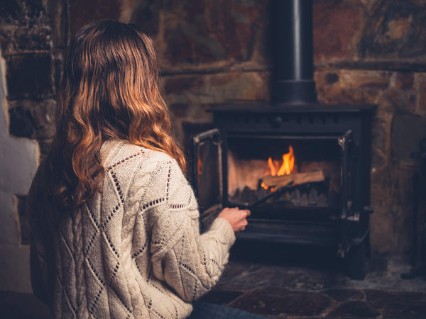 Woman Sat In Front Of An Indoor Wood Burning Stove