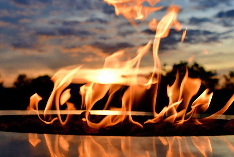 a summer sky sunset as seen through the flames of a fire pit table