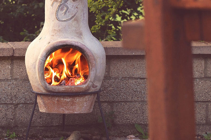 new_log fire burning in a clay chiminea