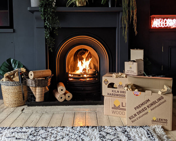 Kiln Dried Kindling and birch logs in a lounge next to a lit fire place