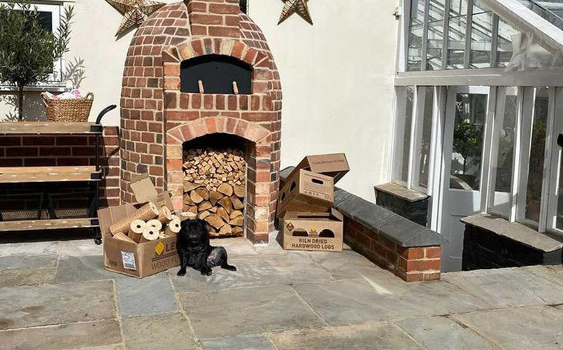 Wood stored under an outdoor wood burner with a dog in front