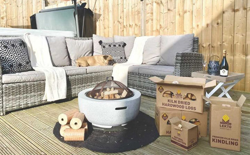 Wooden Decking with dog sleeping on Garden Corner sofa in front of a fire pit surrounded by Kiln Dried Hardwood and fire kindling