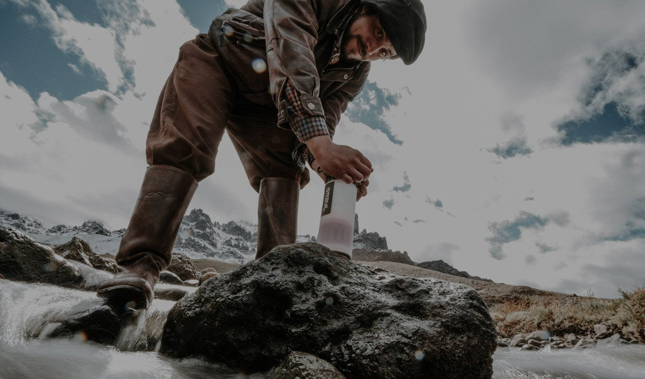 Man in mountains using a Grayl Geopress water filter.