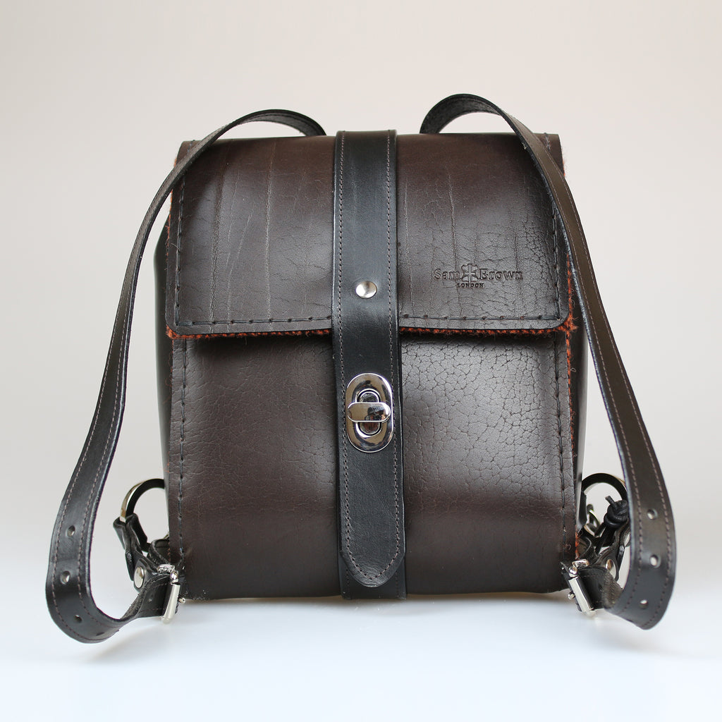 The Malvern Backpack traditional British brown full grain bridle leather hand stitched in black waxed linen Harris Tweed liner & pockets made by Sam Brown London in Wiltshire UK