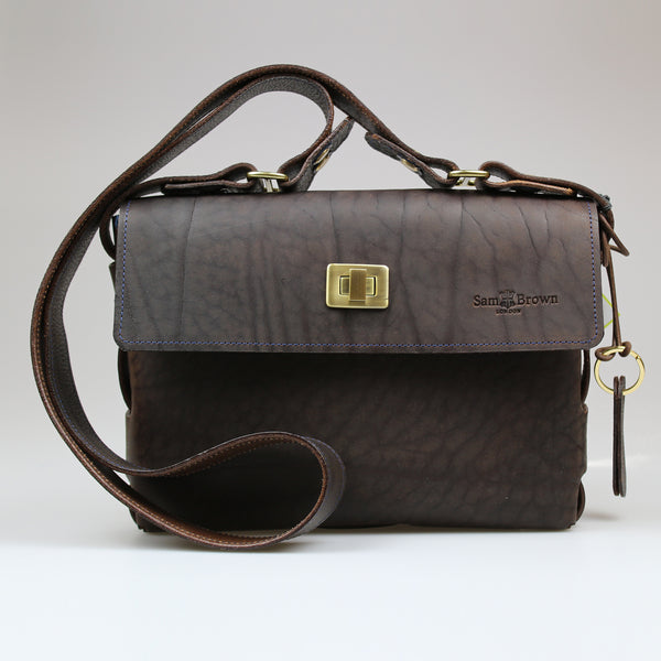 Unisex The Poacher Bag in British oiled brown bridel leather with cross body strap brushed brass fixings & blue Irish linen lining Sam Brown London