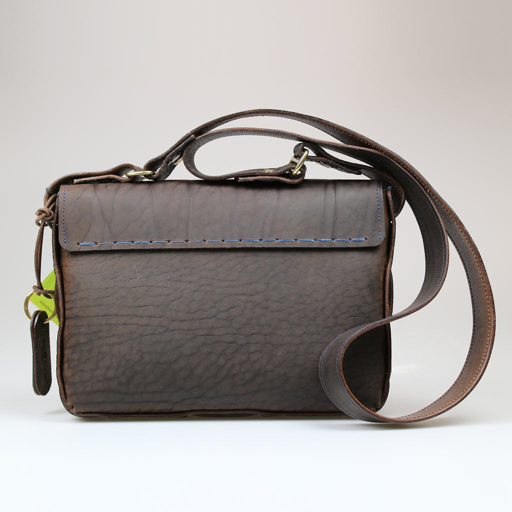 rear view The Poacher Bag in British oiled brown bridle leather with across body strap brushed brass fixings & blue Irish linen lining Sam Brown London