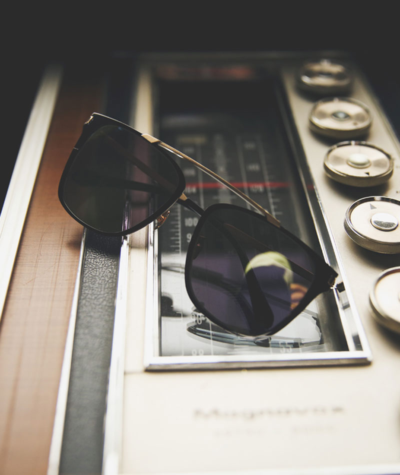 Black square sunglasses with bold metal bridge on top of recording studio equipment.