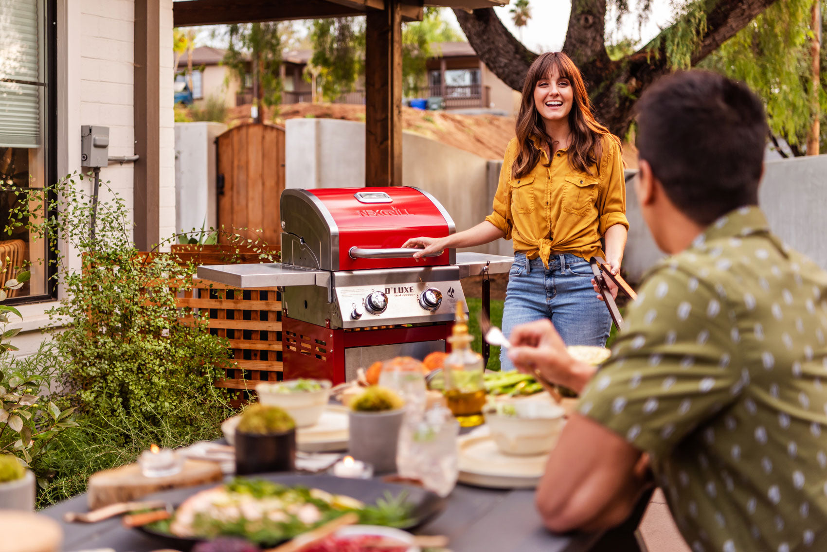 young couple grilling on their Nexgrill DEluxe 2-burner red gas grill
