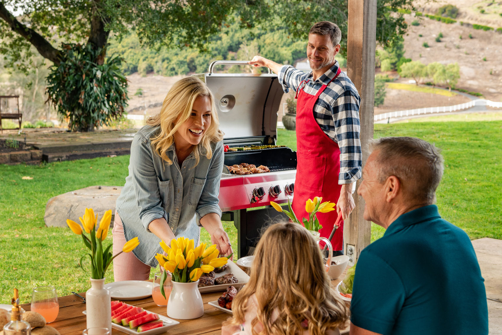 Family grilling in the backyard on the Nexgrill 5-burner gas grill